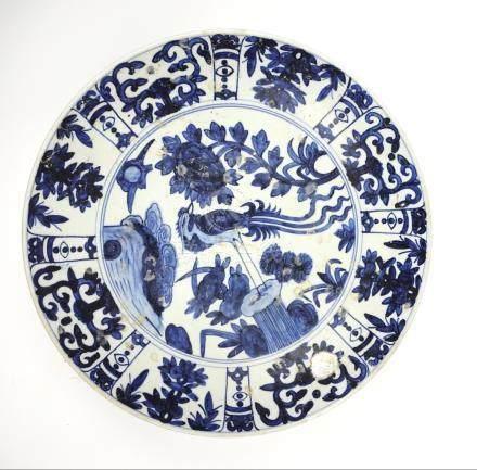 Grand plat en porcelaine blanc bleu. Bord côtelé à décor de phénix. Traces de c