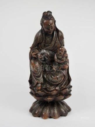 Grand groupe en bois exotique sculpté représentant une divinité portant un enfa