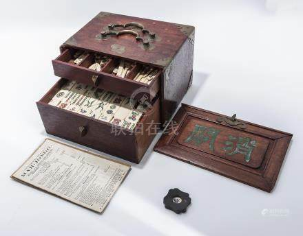A bone and bamboo mahjong set in a decorated wooden case