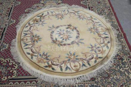 A circular Chinese rug With embossed floral decoration within a tasseled border, diameter 186cm.