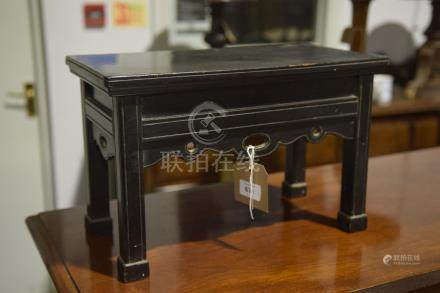 An early 20th century ebonised Chinese urn stand The rectangular top raised upon legs of square