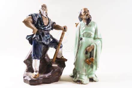 Two Chinese Shiwan (mud man) figures, one standing on a rocky base with an axe