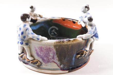 A 19th century Chinese porcelain bowl with figures peering over the rim,