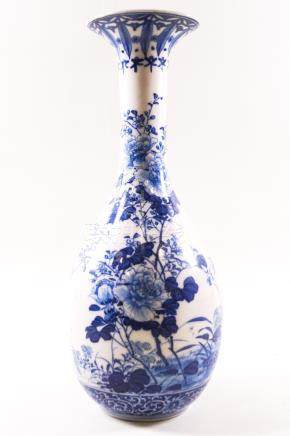 An early 20th century Chinese porcelain vase, painted in over glazed blue enamels with flowers,