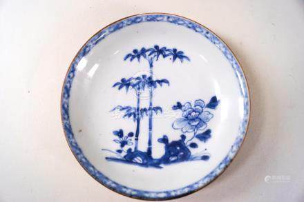 A Nanking cargo porcelain saucer, painted in underglaze blue with a peony and bamboo,