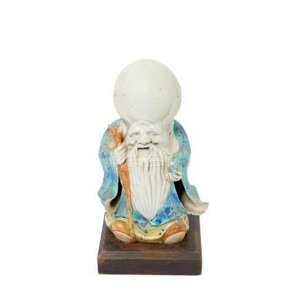Shou Xing. Dios de la longevidad. Figura en cerámica china esmaltada sobre peana en madera, primer