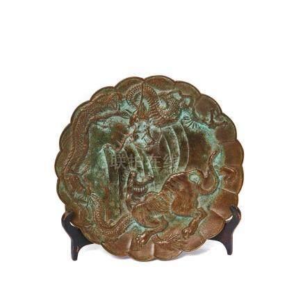 Plato oriental de perfil ondulado en bronce patinado con representación de tigre y dragón en