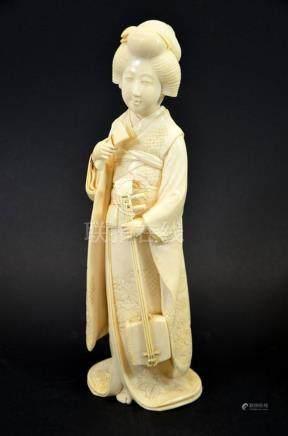 λ A 19th century Japanese carved ivory okimono of a Geisha,