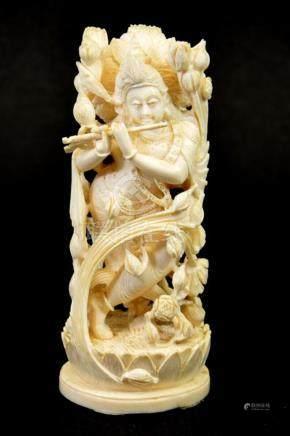 λ A 19th century Indian carved ivory figure of a deity playi
