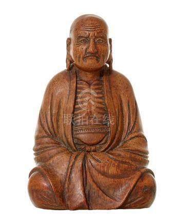 A JAPANESE CARVED BAMBOO FIGURE OF DARUMA EDO PERIOD, CIRCA