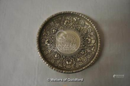 A Chinese white metal dish with coin inset to the centre.