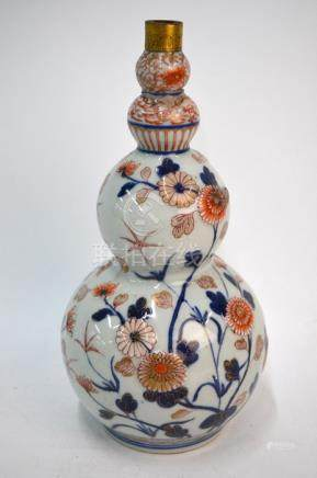 A Japanese Imari vase of gourd form, decorated in underglaze blue, orange and gilt with floral