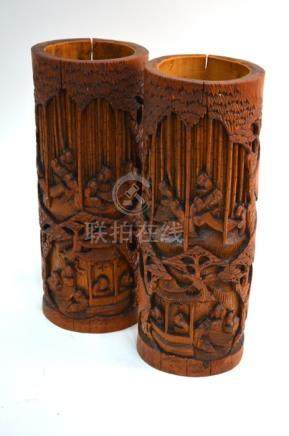 A pair of Chinese bamboo bitongs; each one of typical cylindrical form decorated with scholars in