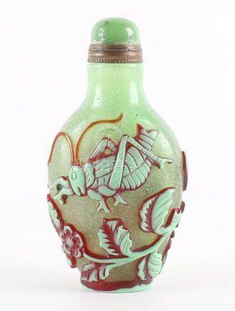 A green / brown overlay snuff bottle with decoration of gras