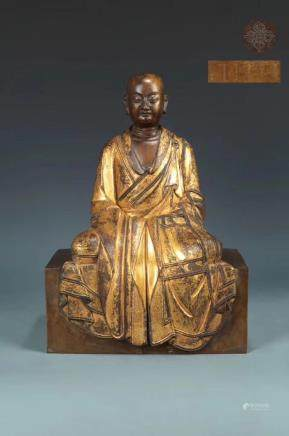 A GILT-BRONZE FIGURE OF SEATED LAMA