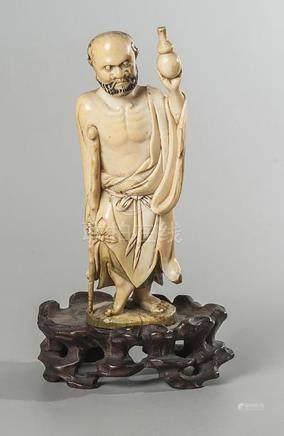 STATUETTE EN IVOIRE représentant un personnage debout appuyé