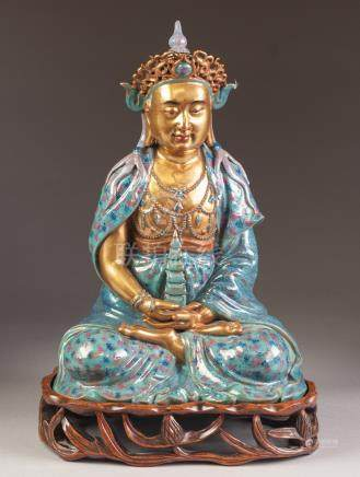 A CHINESE LATE QING/REPUBLIC PERIOD PORCELAIN MODEL OF A BUDDHA seated cross legged holding in the