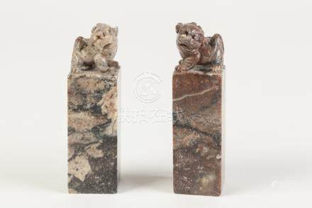 A NEAR PAIR OF CHINESE MOTTLED PURPLISH HARDSTONE SQUARE SEALS, surmounted with Buddhistic lions,
