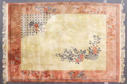 A LARGE CHINESE CARPET, beige ground with floral decoration, with a similar peach ground border.