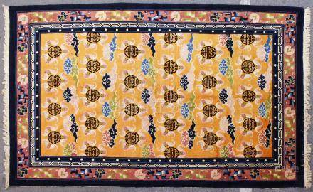 A CHINESE CARPET, peach ground decorated with emblems and clouds. 9ft 0ins x 6ft 0ins.