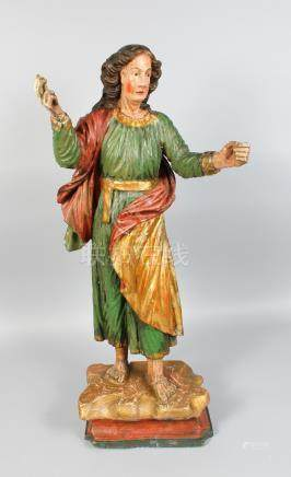 AN 18TH CENTURY CARVED AND PAINTED FIGURE OF A GIRL in flowing robe, her arms outstretched. 31ins