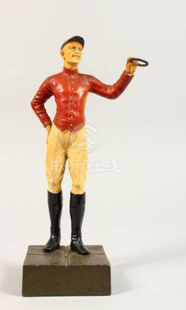 A PAINTED BRONZE STANDING FIGURE OF A JOCKEY, in a red jacket, on a square base. 10.5ins high.