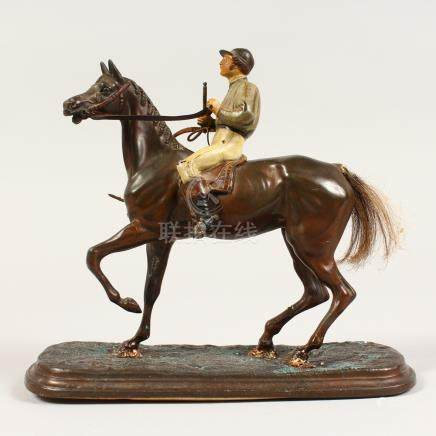 A PAINTED METAL FIGURE OF A JOCKEY ON A HORSE, with painted decoration. 7.5ins high.