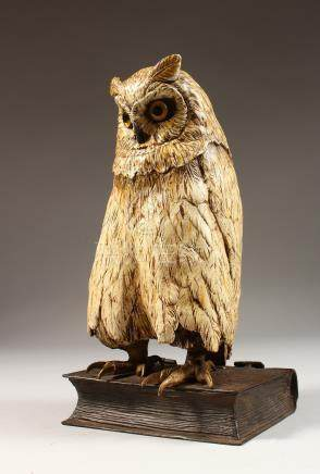 A GOOD AUSTRIAN PAINTED COLD CAST OWL, standing on a book. 11ins high.