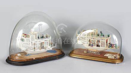 A PAIR OF CHINESE CARVED AND PIERCED IVORY PLEASURE BOATS. 14ins long, in a glass dome.