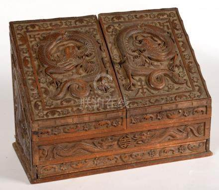 A CHINESE CARVED WOOD SLOPE-FRONT STATIONERY BOX, EACH DOOR CARVED WITH A DRAGON BORDERED BY BATS
