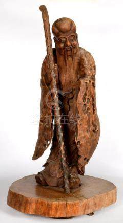 A CHINESE CARVED ROOT WOOD FIGURE OF AN IMMORTAL ON A BASE, EARLY 20TH C, 75CM H