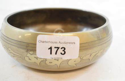 A Tibetan silver coloured metal inlaid bowl, decorated scripture, 12.5 cm diameter