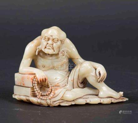 A carved soapstone figure of a wiseman with prayer beads, China, Qing Dynasty, late 19th century