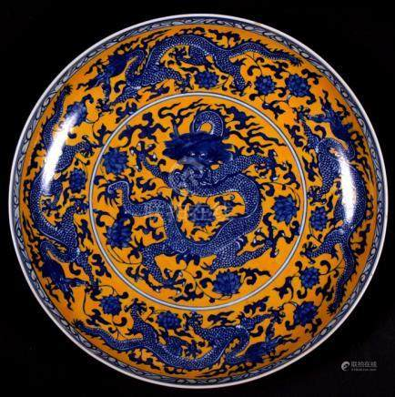 A large Chinese shallow bowl decorated with dragons on a yellow ground, blue seal mark to underside,