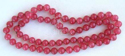 A Chinese pink glass bead necklace.