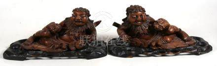 A pair of Chinese carved hardwood groups depicting recumbent figures and their familiars, on