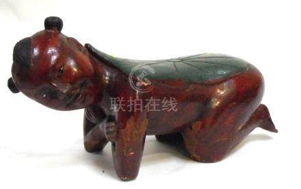 A Chinese polychrome and lacquer carved wooden head rest or pillow in the form of a kneeling boy,