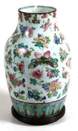 A 19th century Chinese famille rose baluster vase decorated with butterflies, fruit and flowers on a