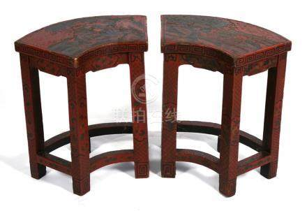 A pair of Chinese red lacquered fan shaped stools decorated with figures in a landscape, 43cms (
