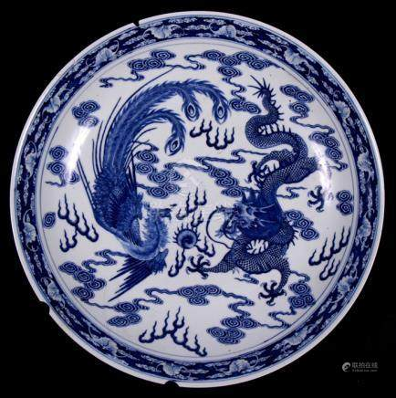 A Chinese blue & white charger decorated with a phoenix and dragon chasing a flaming pearl amongst