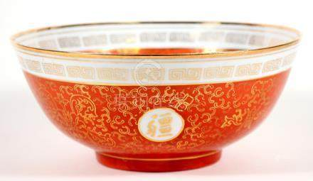 A Chinese bowl decorated with gilded characters and foliate scrolls, on a red ground, 26cms (10.
