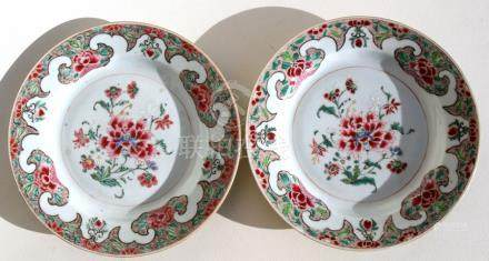 A pair of early 18th century famille rose plates decorated with peonies, 23cms (9ins) diameter.