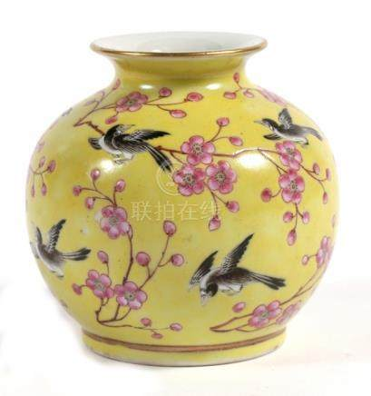 A Chinese vase decorated with birds and prunus on a yellow ground, red four-character mark to