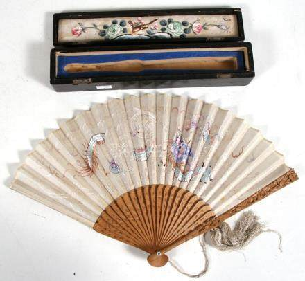 A Chinese carved sandalwood fan with embroidered decoration depicting a dragon chasing a flaming