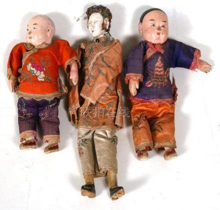A Chinese painted wooden doll in a silk court robe and two similar children, the largest 25.5cms (