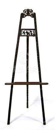 A large Chinese carved hardwood easel decorated throughout with prunus and fruit, 163cms (64ins)