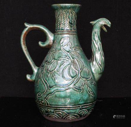 A Chinese green crackle glazed wine pot or ewer decorated with fruit and a phoenix spout, 19cms (7.