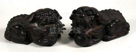 A pair of Chinese carved wood Buddhistic lions, 32cms(12.5ins) long.