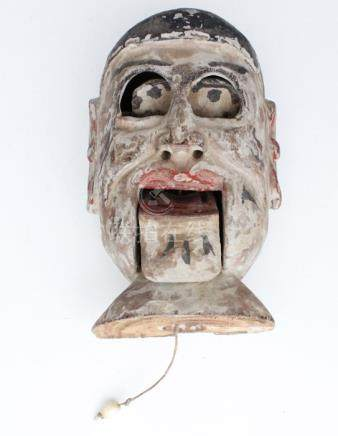 A 19th century Chinese carved painted wooden puppet head with pull-string mouth, 15cms (6ins) high.