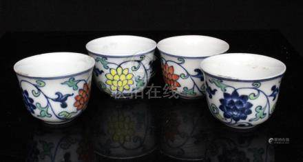 A set of four Chinese Doucai porcelain cups decorated with flowers in foliage, 4cms (1.5ins) high.